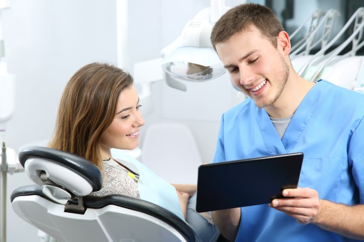 A dentist show shis patient something on a tablet