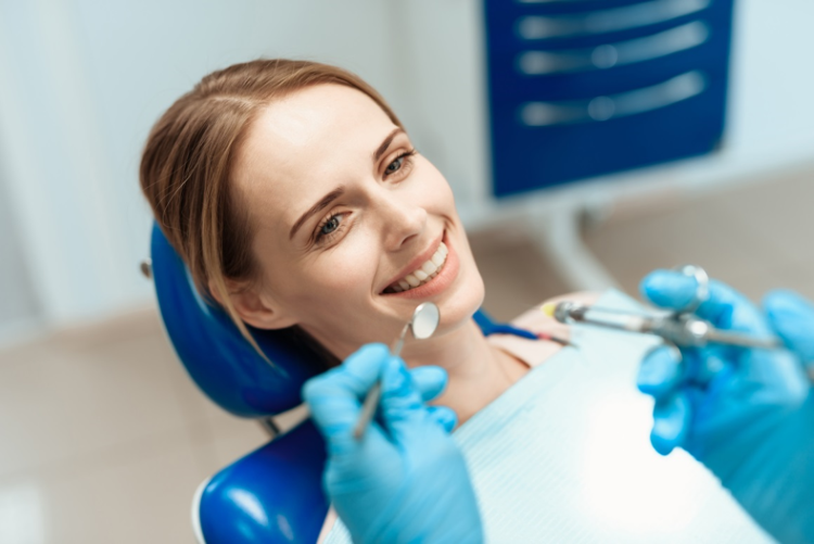 A woman in a dentist chair looks suspiciously happy about the needle the dentist is about to stick into her mouth.